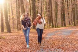 Zwei frohe Frauen, die durch einen Park laufen