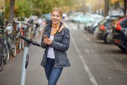 Young woman in the street with e-scooter