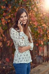 Smiling young woman chatting on a mobile in autumn