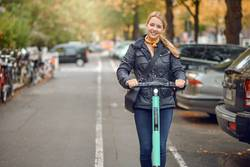 Young happy woman riding an electric scooter in the city