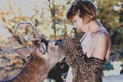 A young blonde boho woman with a deer