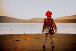 a young woman with red hat in a romantic sunset in a lake