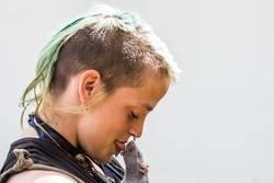 A young woman kissing a rat close up