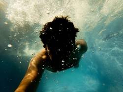 Underwater Photo. A man diving in a pool in summer time