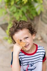 Child playing with an autumn fall leaf