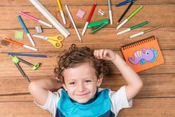 Child surrounded by school supplies