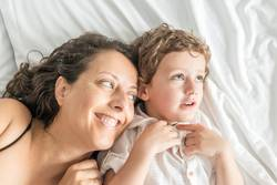 A woman and her son playing in bed and gesturing.