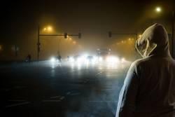 ein Mann beobachtet nachts den Strassenverkehr