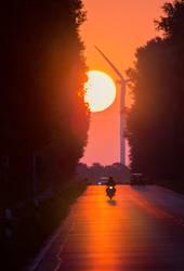 ein Sonnenaufgang an einer Landstrasse mit Fahrzeugverkehr