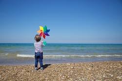 Child from behind holds a colorful pinwheel in front of the sea
