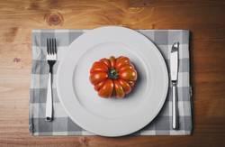Red tomato on white plat