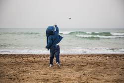 Child throws a stone in the sea