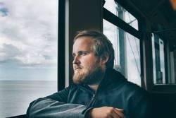 Mathias | Mann mit Bart schaut aus dem Fenster im Zug
