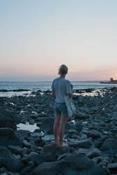 Alexa | Junge Frau schaut am Meer in den Sonnenuntergang