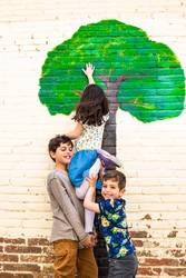 Three kids playing with a tree painted on a wall