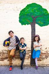 Portrait of three kids with a painted tree background