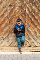 Little boy with a mibile phone with a wooden door background