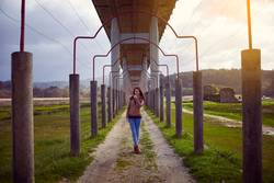 Young girl posing under a bridge in the nature