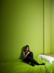 Young woman alone on a green high ceiling room