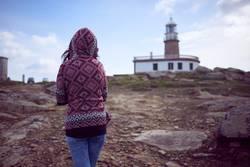 Woman walking towards a lighthouse