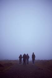 A group of people walking into the fog