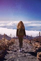 Woman walking on Teide Mountain, with the stars in the sky