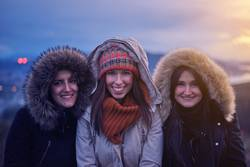 Three young women smiling at sunset in winter