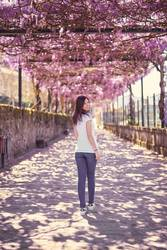 Young woman walking under a flower roof