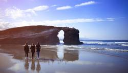 Three young women walking in the Beach of the Cathedrals