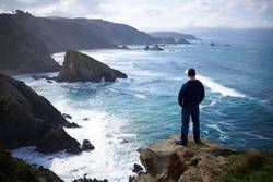 Man contemplating the ocean from a cliff