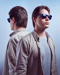 Young man with sunglasses back to back with his reflection
