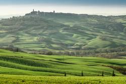 Majestätisches grünes Tal mit Stadt auf dem Gipfel