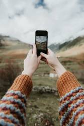 Woman taking photo on smartphone of valley with high hills in cloudy weather