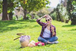 Front view of a young hipster woman sitting on grass in a park while holding a flower and smiling in a sunny day