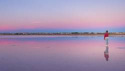 Frau, die den schönen Himmel am leeren Strand bewundert.