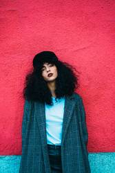 Stylish curly woman at colorful wall