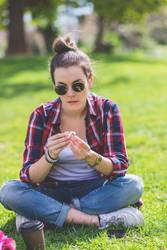 Front view of a young hipster woman sitting on grass in a park while holding a flower in a sunny day