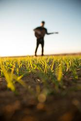 Man with guitar on field
