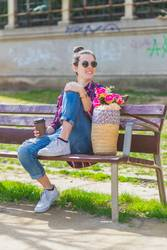 Front view of a young hipster woman sitting on a park bench relaxing in a sunny day while looking away