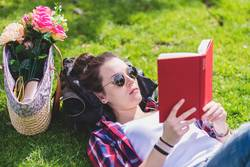 Side view of a hipster happy woman lying on grass in sunny day at park while reading a red book