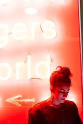 Attraktive, stylische Dame mit Smartphone in der Nähe von Neonröhren.