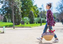 Side view of a young hipster woman holding a wicker basket while walking in a park in sunny day
