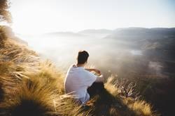 Mann auf dem Hügel sitzend