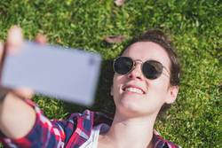 Above view of a young smiling hipster woman lying on grass in a sunny day at a park while taking a selfie with a mobile phone