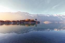 Ruhiger See mit Booten auf dem Pier gegen die Berge
