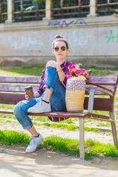 Front view of a young hipster woman sitting on a park bench relaxing in a sunny day while looking to camera