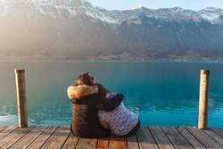 Frauen auf dem Pier in den Bergen umarmen