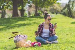 Front view of a young hipster woman wearing sunglasses, sitting on grass in a park while using a mobile phone