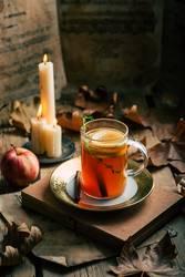 Tee in der Nähe von Kerzen und Äpfeln