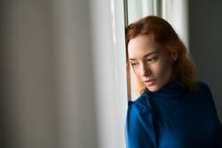Nachdenkliche Frau am Fenster